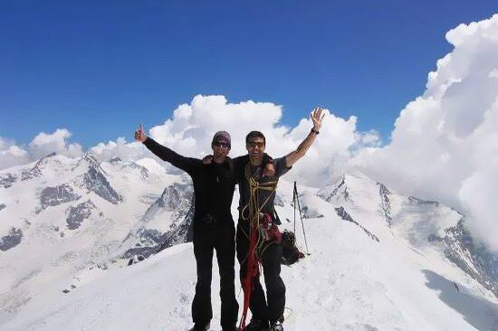 Dos chicos haciendo cima en la montaña